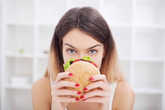 Dieet. jonge vrouw met duct tape over haar mond, waardoor ze junkfood niet kan eten. gezond eten
