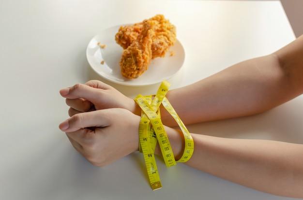 Dieet. jonge vrouw slank lichaam handen vastgebonden met geel meetlint en heerlijke krokante gebakken kip in schotel op het bureau in de keuken thuis