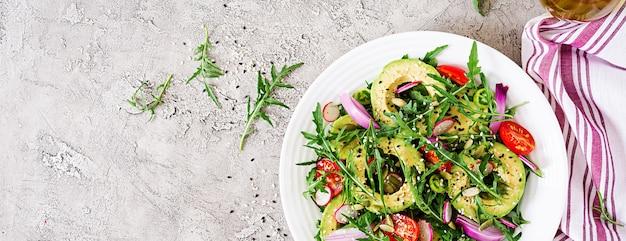 Dieet menu. gezonde salade van verse groenten - tomaten, avocado, rucola, radijs en zaden op een kom. veganistisch eten. plat liggen. bovenaanzicht