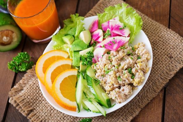Dieet menu. ontbijt. havermoutpap met groenten (komkommer, avocado, daikon) en sinaasappel