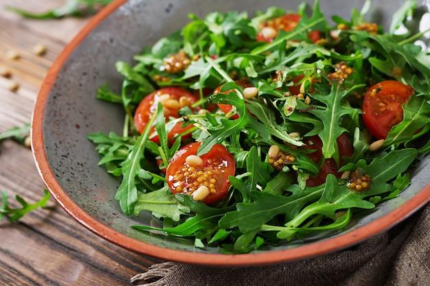Dieet menu. veganistische keuken. gezonde salade met rucola, tomaten en pijnboompitten.