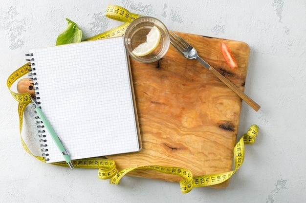Dieet plan concept. leeg notitieboekje met het meten van band op een houten scherpe raad. bovenaanzicht