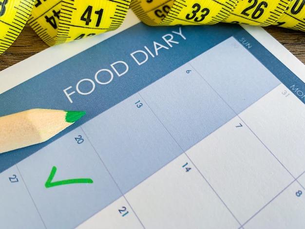Dieet plan . het meten van band en dieetplan op houten achtergrond.