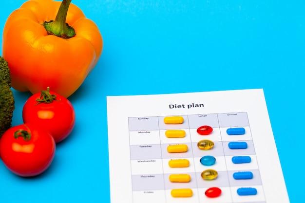 Dieet plan, voor gewichtsverlies pillen en verse groenten op blauw.