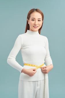 Dieet, sport en gezondheid concept - mooie sportieve vrouw met meetlint Premium Foto