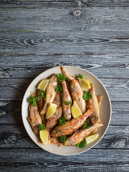 Dieet surmullet vis. gebakken vis in een bord op een donkere houten tafel.