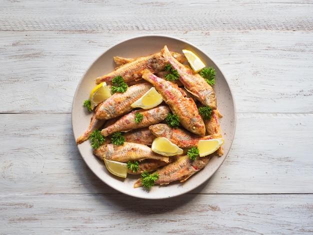 Dieet surmullet vis. gebakken vis in een plaat op een witte houten achtergrond.