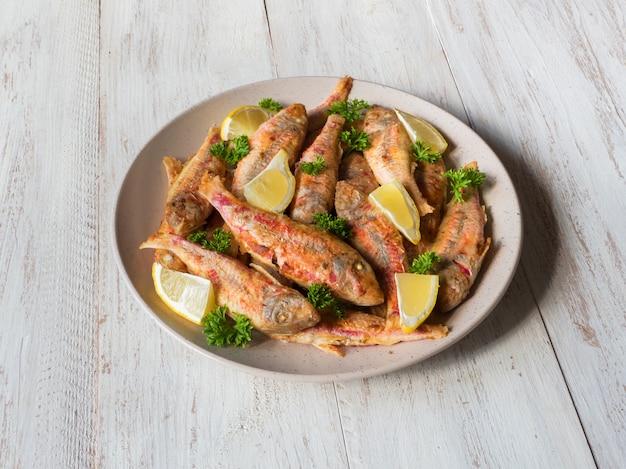 Dieet surmullet vis. gebakken vis in een plaat op een witte houten tafel.