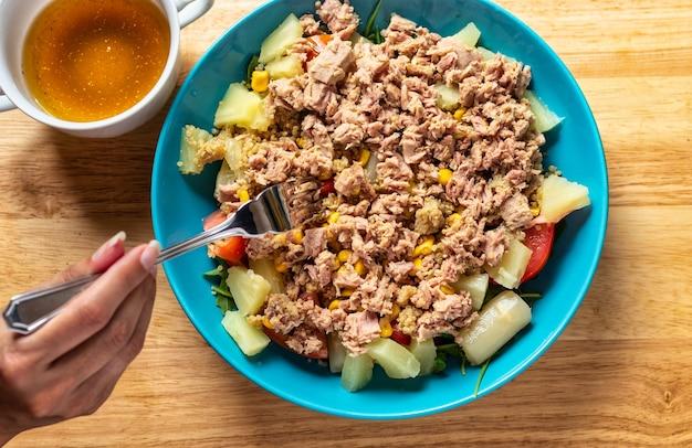 Dieet tonijnsalade met groenten en kruidensaus ernaast.