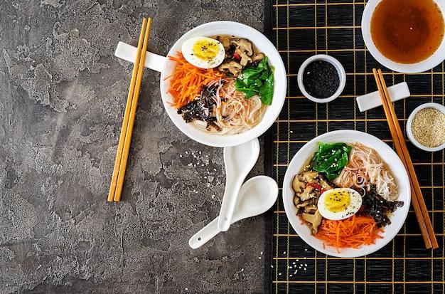 Dieet vegetarische kom noedelsoep van shiitake-champignons, wortel en gekookte eieren. japans eten. bovenaanzicht plat leggen