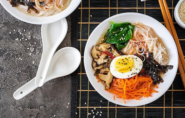 Dieet vegetarische kom noodle soep van shiitake paddestoelen, wortel en gekookte eieren. japans eten. bovenaanzicht. plat leggen
