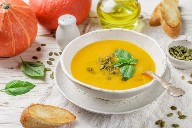 Dieet vegetarische pompoenroomsoeppuree met olijfolie, zaden en basilicum