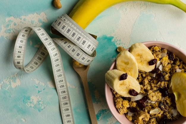 Diëet voeding. gezond ontbijt. havermout met fruit en noten. taille meter.