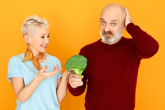 Dieet, voeding, gezondheid, biologische producten en vegetarisme concept. gefrustreerde senior man kijkt naar camera met treurige gezichtsuitdrukking, houdt walgelijke broccoli vast, zijn vrouw laat hem greens eten