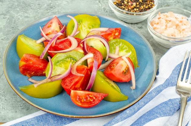 Diëet voeding. salade van plakjes verse heldere tomaten en uien. studiofoto.