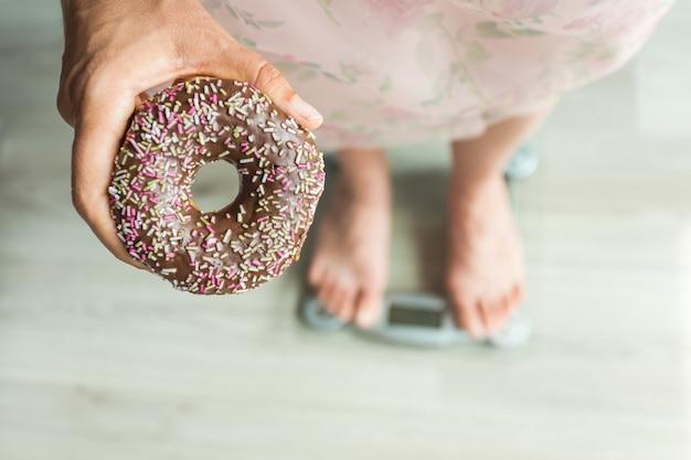 Dieetconcept. close-up van de voeten van de vrouw op weegschaal met donut. concept van snoep, ongezond junkfood en obesitas.