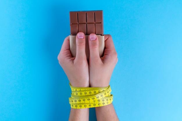Dieetconcept, gewicht verliezen, chocolade in de handen die met gele metende band worden gebonden