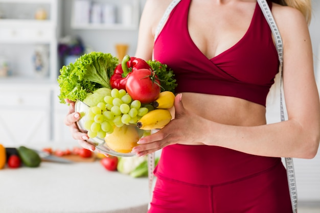 Dieetconcept met sportieve vrouw in keuken