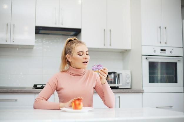 Dieetconcept, mooie jonge vrouw die tussen gezond voedsel en ongezonde kost kiezen