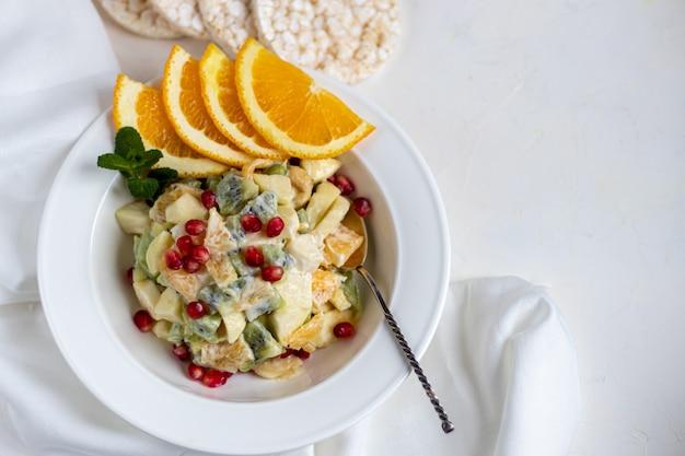 Dieetfruitsalade voor ontbijt. kiwi sinaasappel banaan en appel in blokjes gesneden en gekruid met yoghurt met honing.