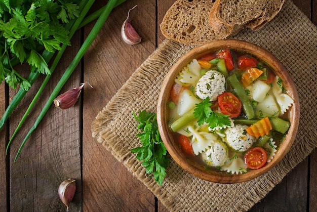Dieetgroentesoep met kippenvleesballetjes en verse kruiden in houten kom