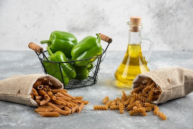 Dieetpasta's in manden met groene paprika's en olijfolie.