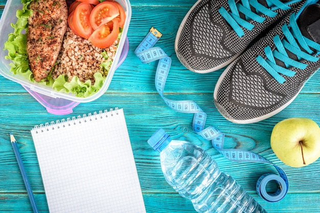 Dieetplan, menu of programma, meetlint, water, lunchdoos met kipfilet, boekweit, tomaten en appel op blauw, plat leggen