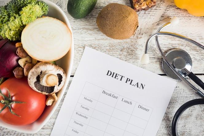 Dieetplan met groenten en stethoscoop op houten bureau