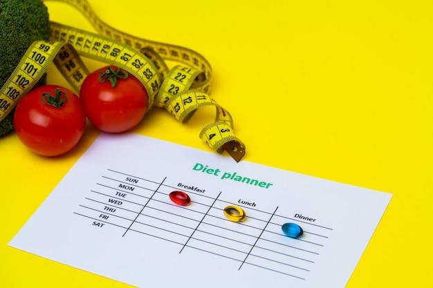 Dieetplan voor gewichtsverlies pillen en verse groenten op geel.
