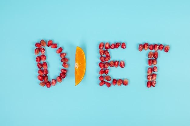 Dieetregeling van fruit granaatappelzaden en sinaasappel op blauwe achtergrond