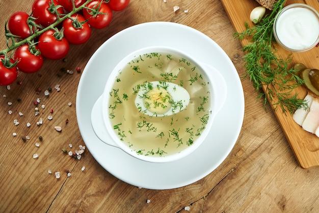 Dieetsoep met kip, gekookt ei groenten en peterselie in compostion met ingrediënten op houten oppervlak in witte kom. bovenaanzicht smakelijke soep. plat gelegd voedsel