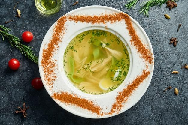 Dieetsoep met kip, gekookte ei groenten en peterselie in compostion met ingrediënten op donkere ondergrond in witte kom