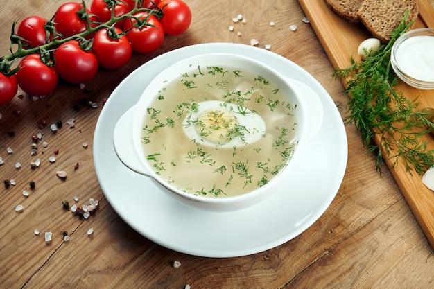Dieetsoep met kip, groenten en peterselie in compostion met ingridients in witte kom. bovenaanzicht smakelijke soep. plat gelegd voedsel