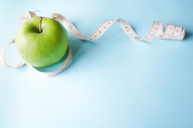 Dieetsymbool plat leggen een meter lint en groene appel.