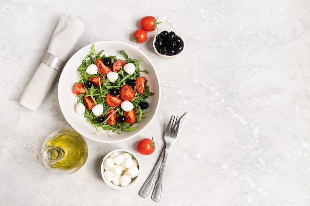 Dieetvoedsel salade met rucola mozzarella tomaten en olijven olijfolie