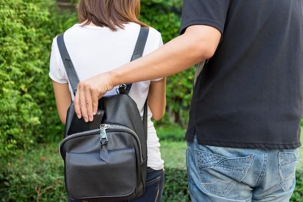 Dief die de portefeuille in de rugzak in het openbare park probeert te stelen.