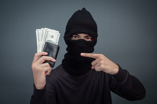Dief draagt een zwarte hoed met een gestolen tas op grijs