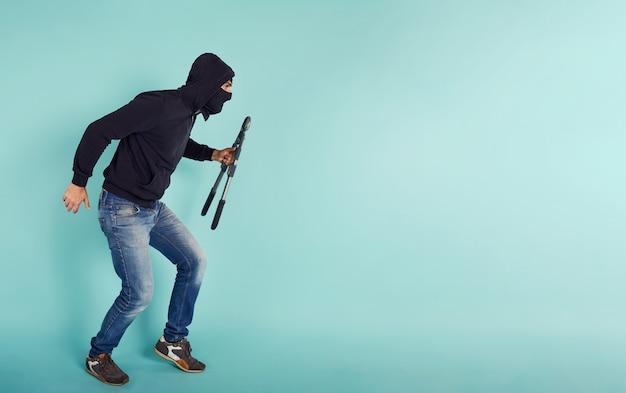 Dief met bivakmuts handelt in stilte om appartementen te stelen met draadknippers in de hand