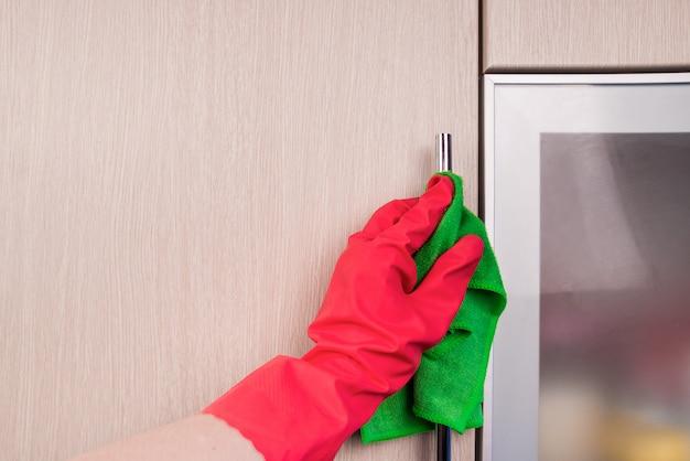 Dien beschermende handschoen in om houten meubels met een doek te reinigen. vroege voorjaarsschoonmaak of regelmatige schoonmaak. meid maakt huis schoon.