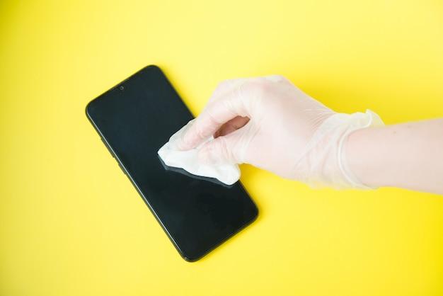 Dien beschermende handschoen met servet in die mobiele telefoon op gele achtergrond schoonmaken. coronavirus desinfectieconceptie.