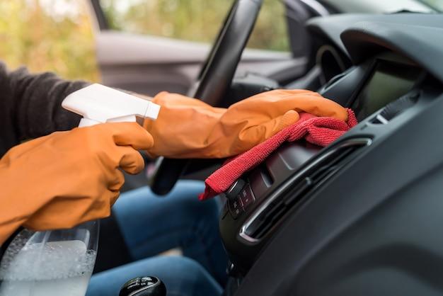 Dien beschermende handschoenen in om het interieur van de auto te reinigen van coronavirus covid-19 met behulp van microvezelkleding. veiligheid