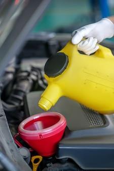 Dien beschermende witte handschoen in met kleine gele bus onder de motorkap van de auto