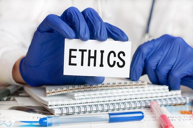 Dien blauwe handschoen met witte kaart in. arts die een witboekkaart met tekst houdt: ethiek. gezondheidszorg conceptueel voor ziekenhuis, kliniek en medische zaken. concept woord ethiek.