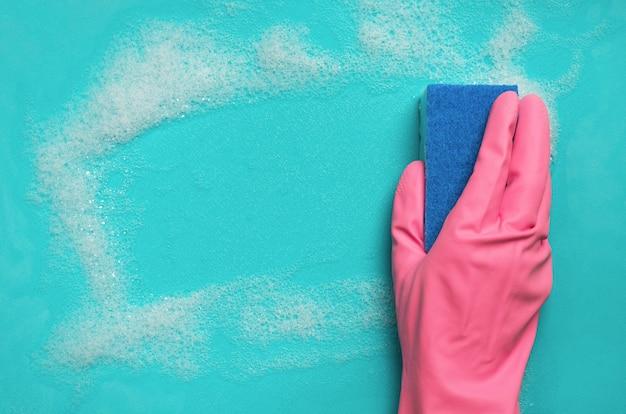Dien de roze rubberen spons van de handschoenholding in en veegt zeepachtig schuim op blauwe oppervlakte af. schoonmaak concept