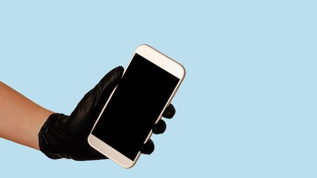 Dien de zwarte smartphone van de handschoenholding met het lege lege scherm op blauwe ruimte in. veilig eten levering concept.