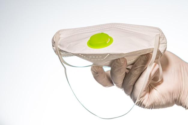 Dien een latexhandschoen in houdend een gezichtsmasker met filter dat op wit wordt geïsoleerd