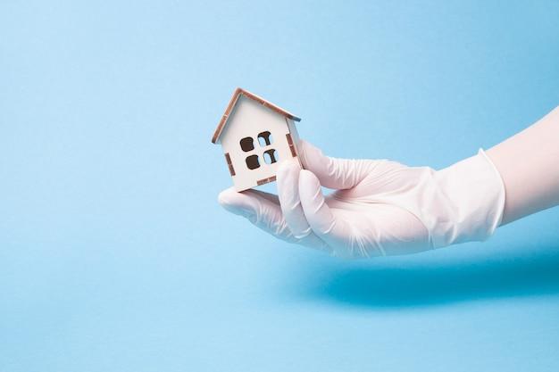 Dien een witte medische rubberhandschoen in houdt een klein houten huis