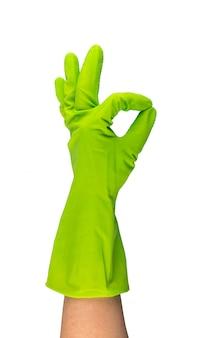 Dien groene beschermende rubberhandschoen in die op witte achtergrond met het knippen van weg wordt geïsoleerd. opgeheven gehandschoende hand met oke gebaar