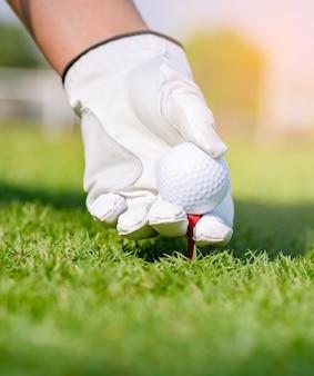 Dien handschoen in die golfbal op t-stuk in cursus plaatst