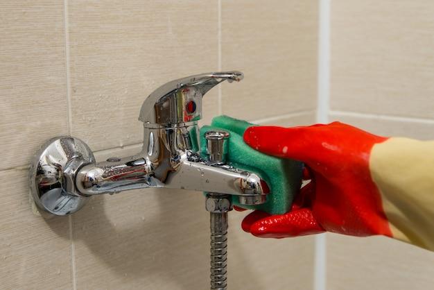 Dien rubberhandschoen in maakt de vuile verkalkte kraan van de douchemengkraan schoon, sluit omhoog foto